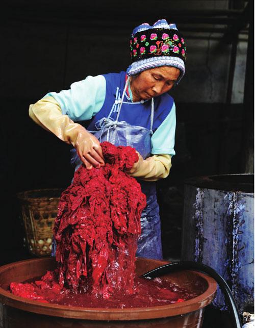 老人正在为布料着色,云南各种特色民族服装和手工艺品的材料正源于这些各式各样的布匹。