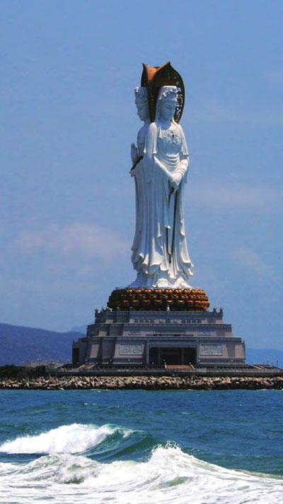 大东海热带风格的酒吧和南山海上的观音塑像。