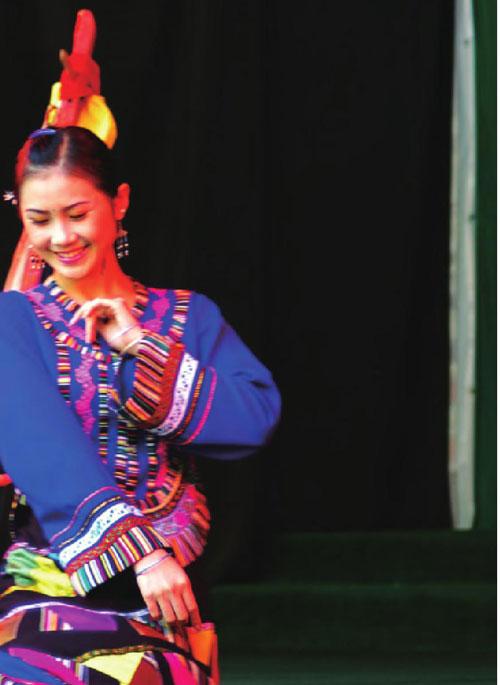 青年女子正跳着傣族舞蹈,她的一颦一簇都那 么动人娇羞。