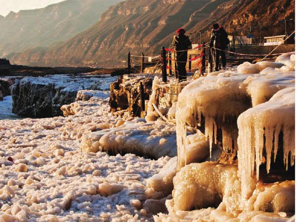 坚硬的冰雪锁住了壶口往日的喧嚣,冻结如柱的流水晶莹剔透,让 瀑布散发着冬日里的温柔典雅。